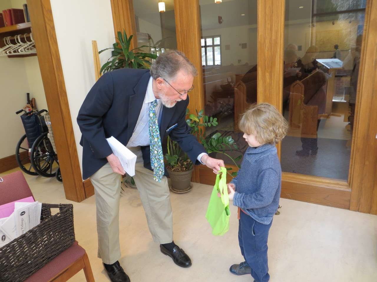 Usher Carl hands out a bag with puzzles and toys for youngsters to use during the service.